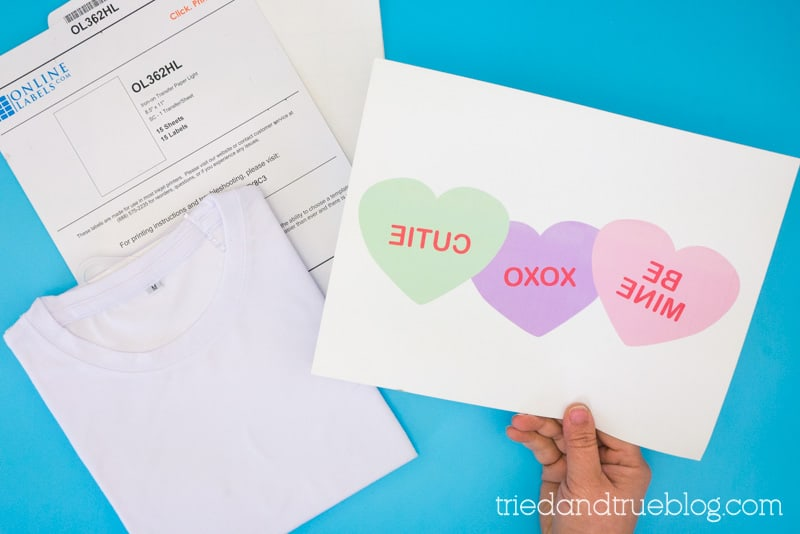 Hand holding iron-on transfer paper with the reversed image of conversation hearts.