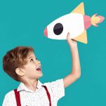 Child holding a paper rocketship.