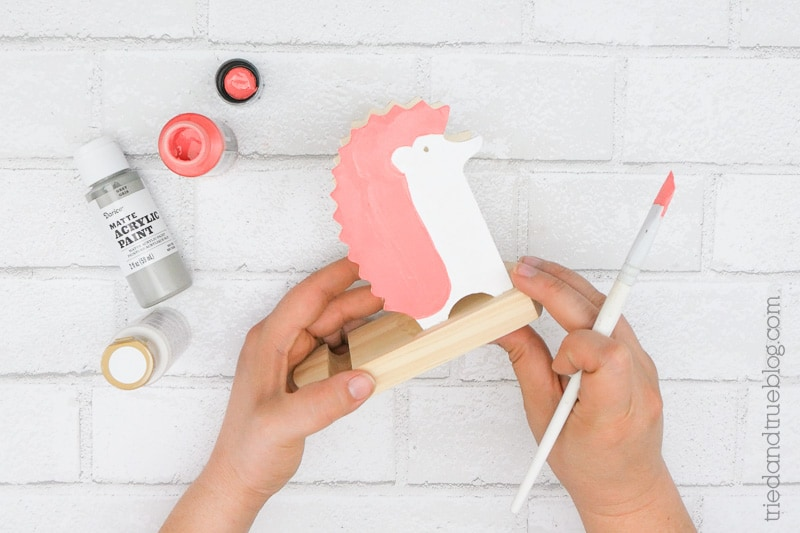 Adding white and pink paint to a blank wood hedgehog.