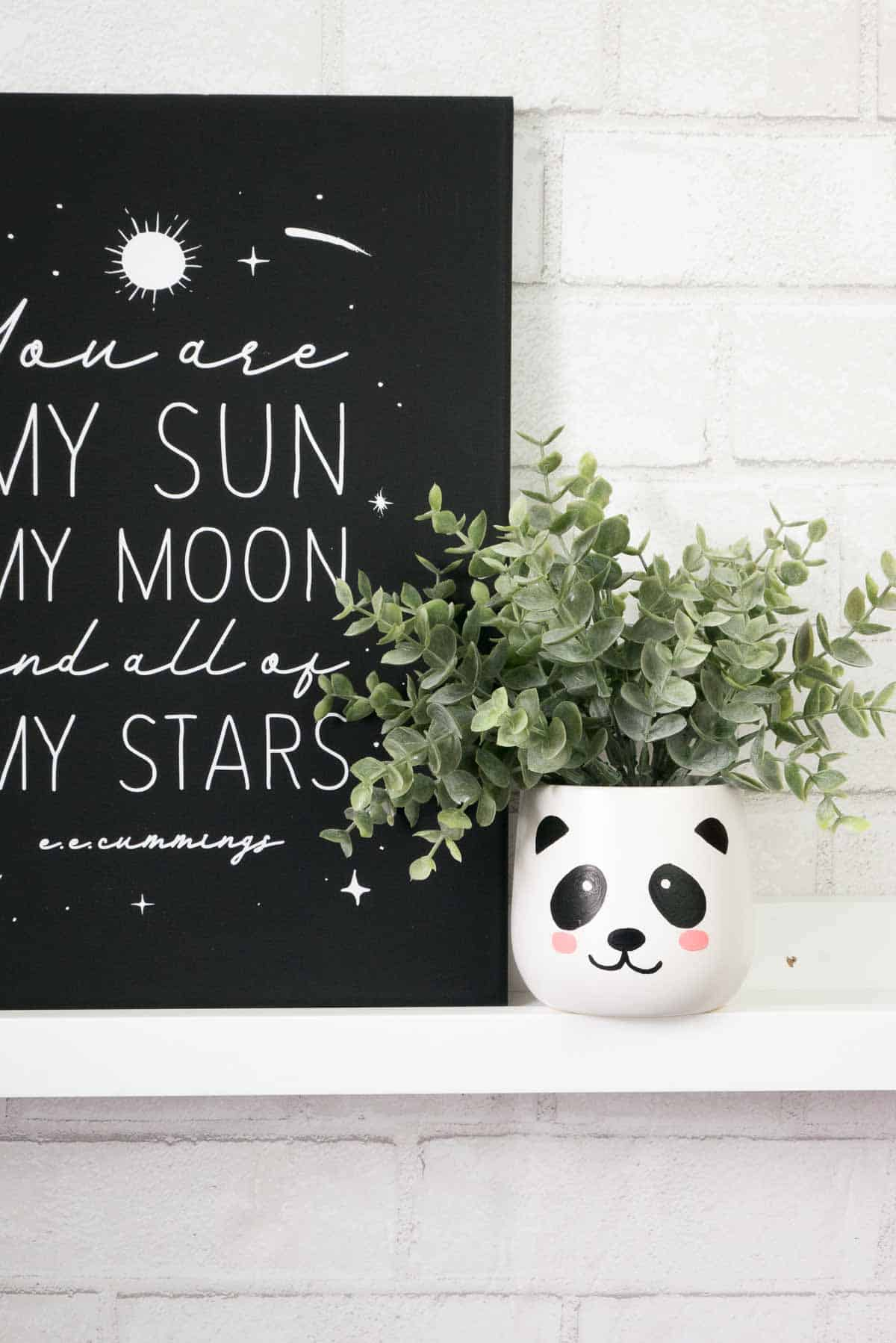 White ceramic planter with painted panda face on a ledge.