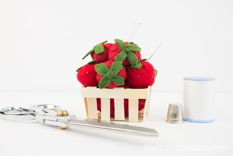 Felt strawberries in a mini berry basket with needles sticking out.