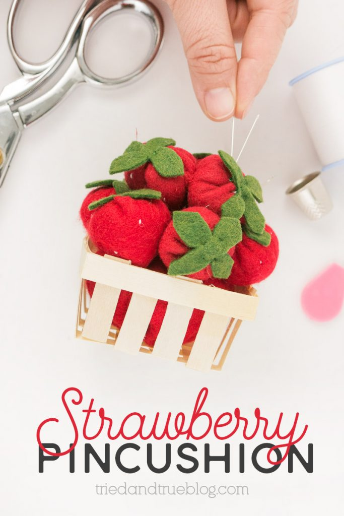 Close up image of hand placing needle into a Strawberry Pincushion.