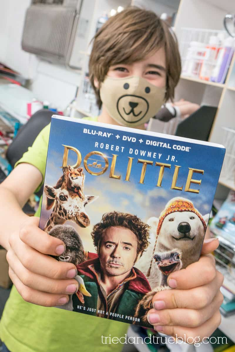 Boy holding Dolittle DVD while wearing a bear face mask.