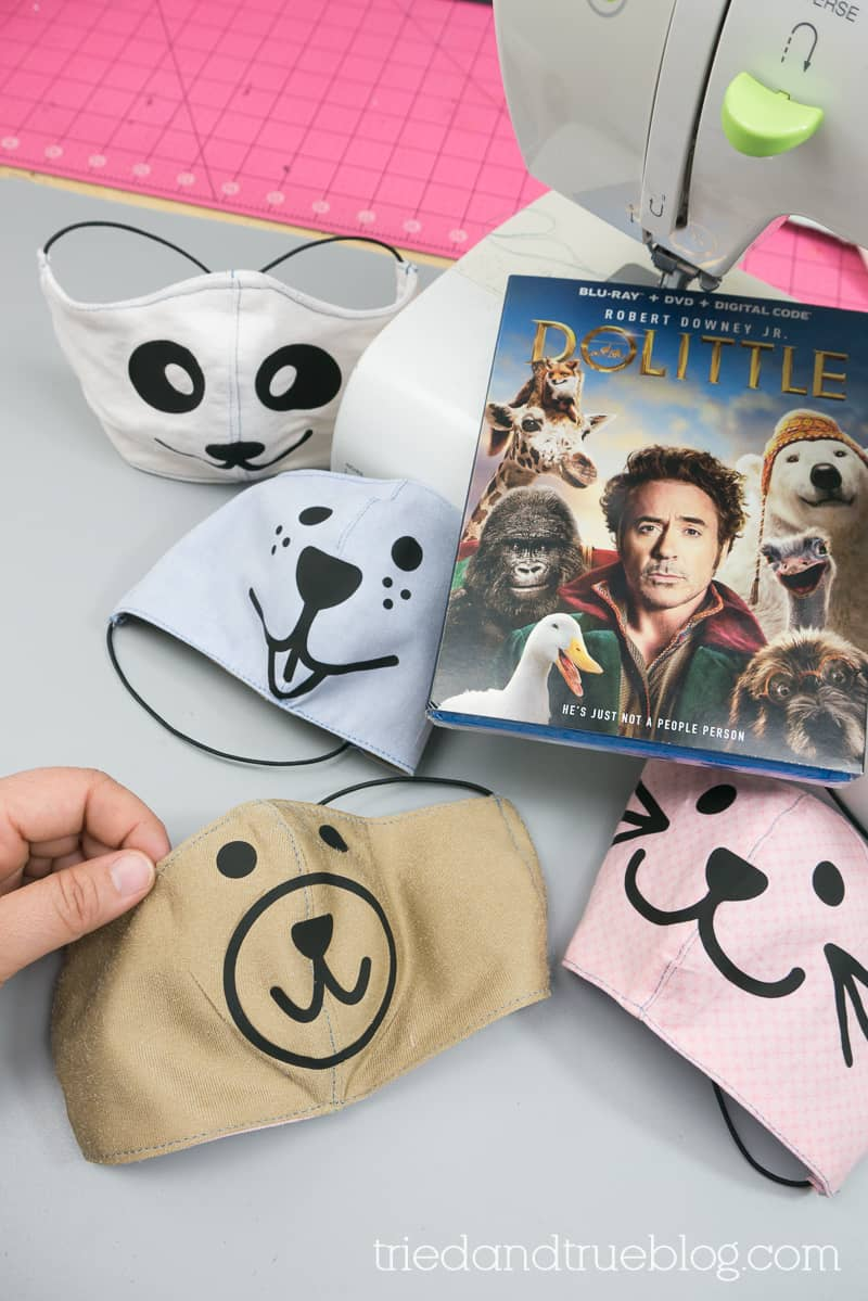 Four Animal Face Masks near a sewing machine with the Dolittle DVD.