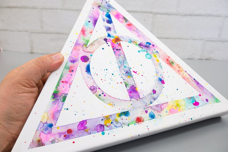 Close up of a hand holding a triangular canvas with watercolor Deathly Hallows logo.