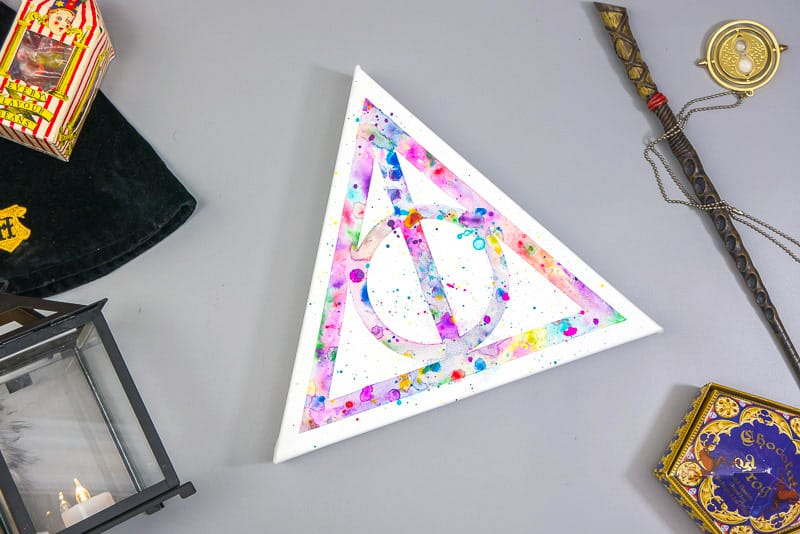 Deathly Hallows watercolor on a gray background.