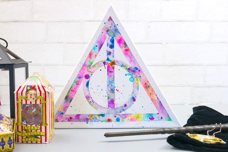 Triangular canvas with Harry Potter Deathly Hallows watercolor art surrounded by other memorabilia.
