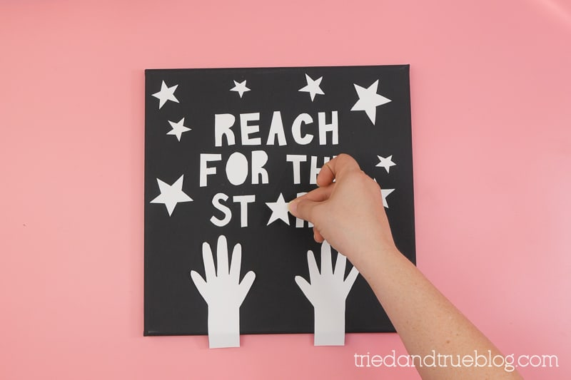 Hand placing a white star on a black canvas with the words,