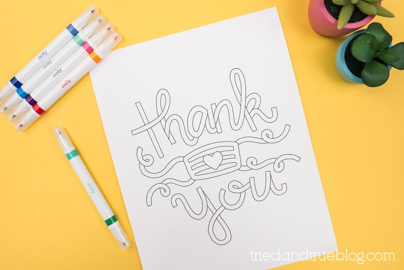 Thank You Essentials Coloring page on a yellow backdrop with markers.
