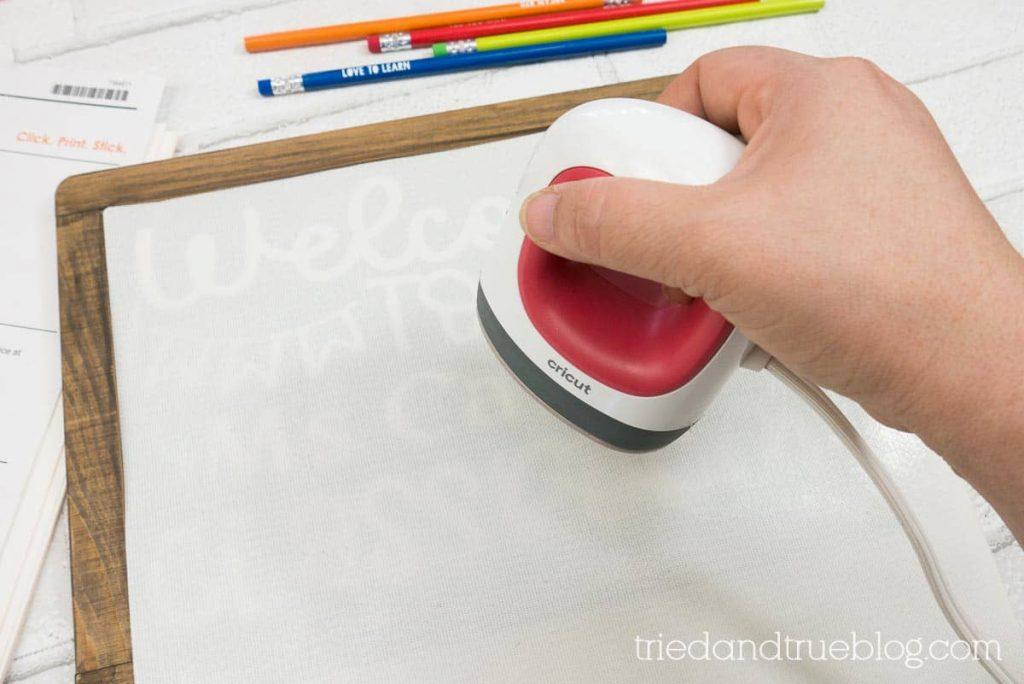 Hand holding an EasyPress Mini on chalkboard.