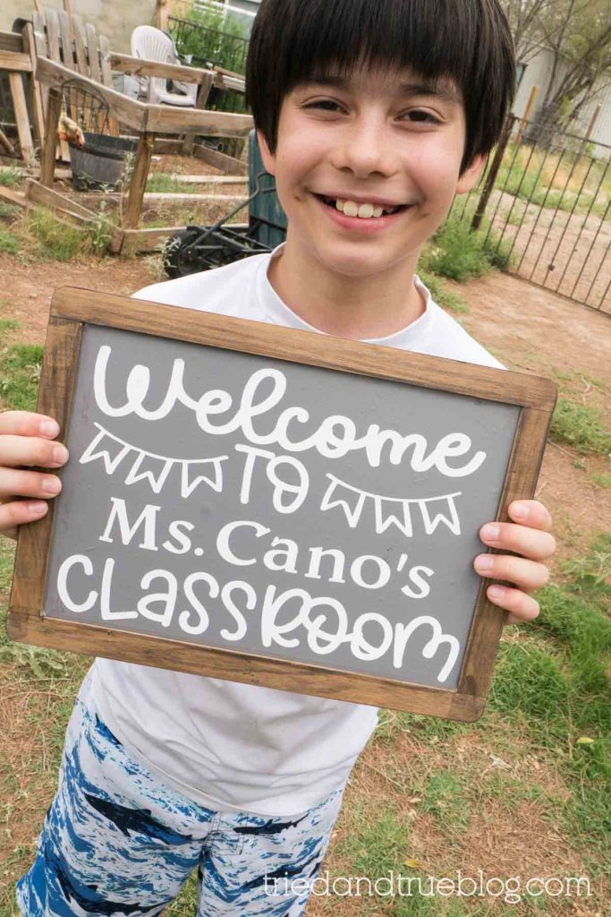 Child holding chalkboard outside with the words