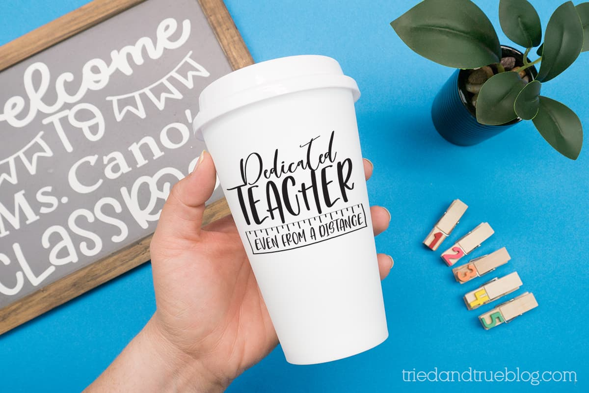 Hand holding a cup on a blue background with the Distance Learning Teacher Free SVG on it.