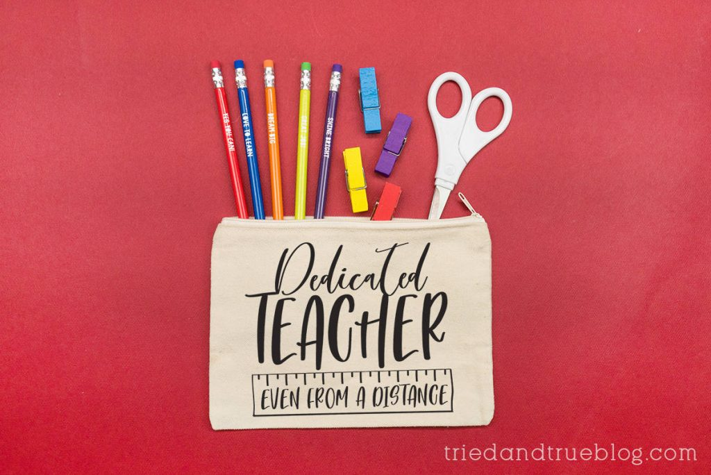 Canvas pouch with school supplies coming out of the top on a red background. Includes the Distance Learning Teacher SVG.