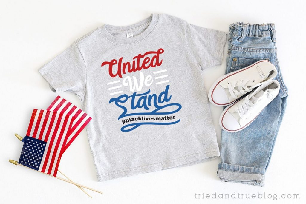 Flat lay with US flags and gray t-shirt with the United We STand Protest Free SVG.