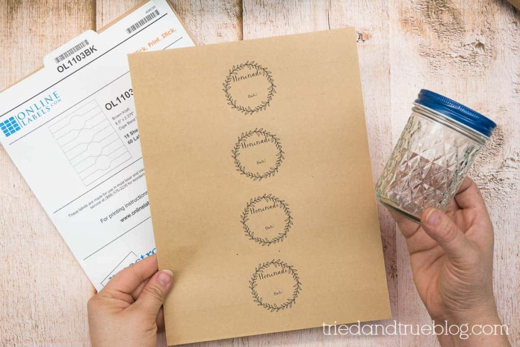 Hand holding a jar and a sheet of printable canning labels.