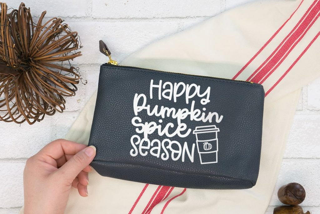 Hand holding black make-up bag with the Pumpkin Spice Season Free SVG