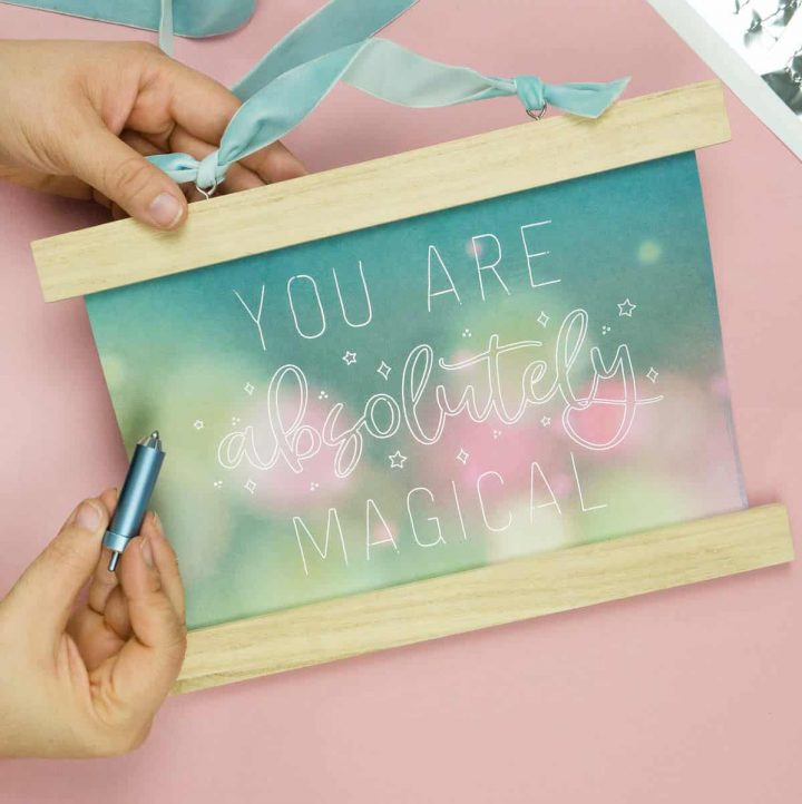 Hand holding Cricut Foil Transfer Tool with two varieties of the You Are Magical Single Line Free SVG.