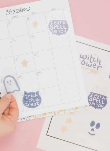 Hand placing cute Halloween free stickers in planner