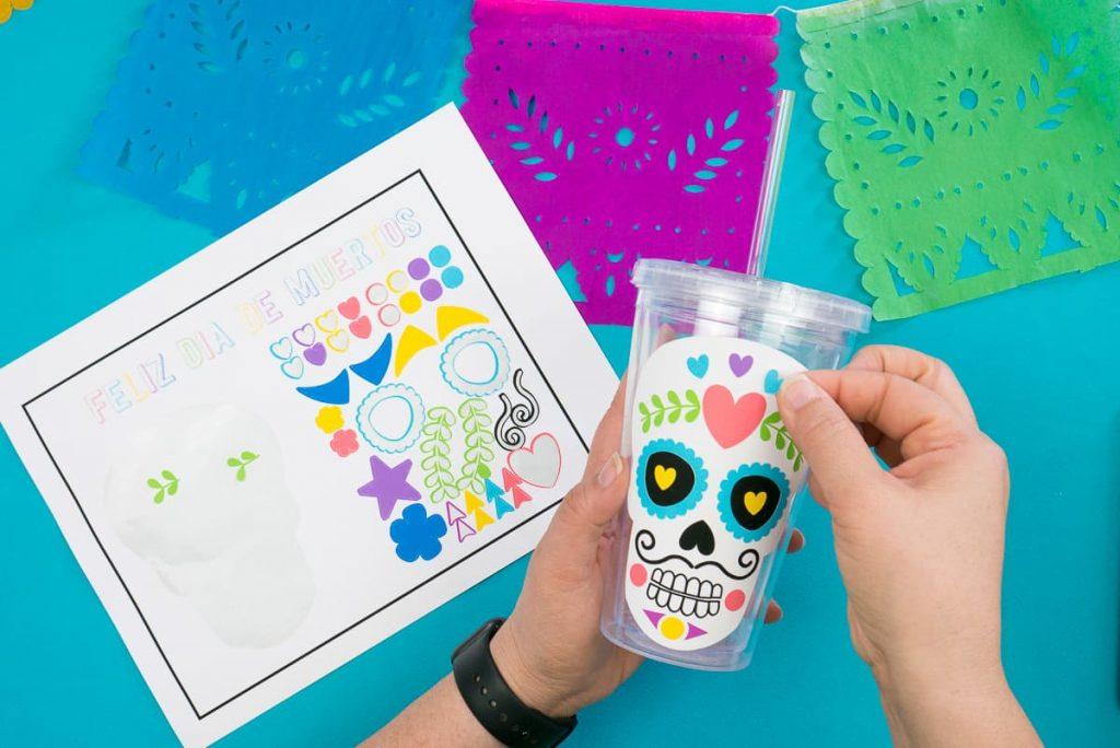 Hand placing Día de Muertos Free Calavera Stickers on a water glass.