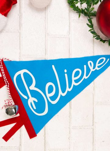 """Blue Felt Christmas Pennant Flag with word """"Believe"""" on a white background."""
