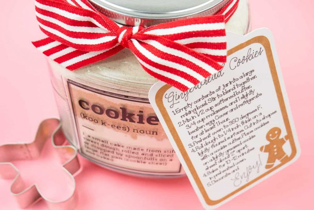 Cookie jar with gingerbread cookie mix on a pink background with a cookie cutter.