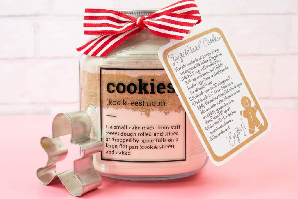 Gingerbread Cookies In a Jar Holiday Gift on a pink background with cookie cutter.
