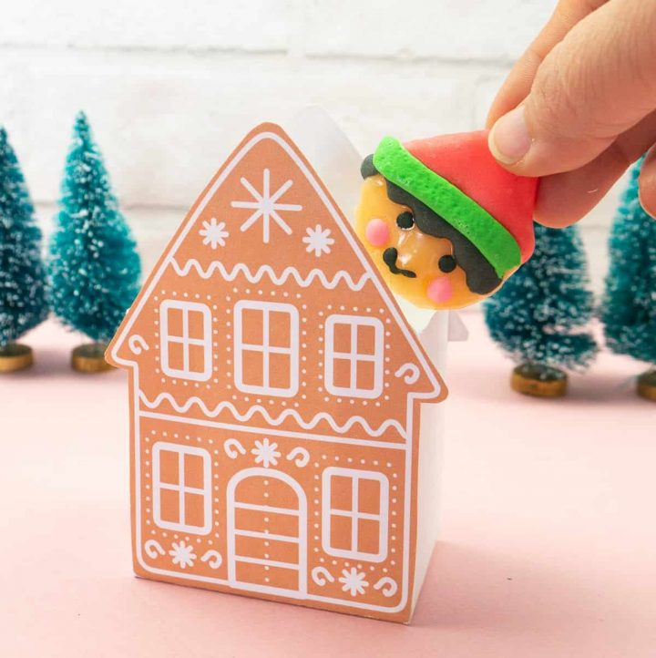 Hand inserting a elf lollypop into a Gingerbread Gift Box.