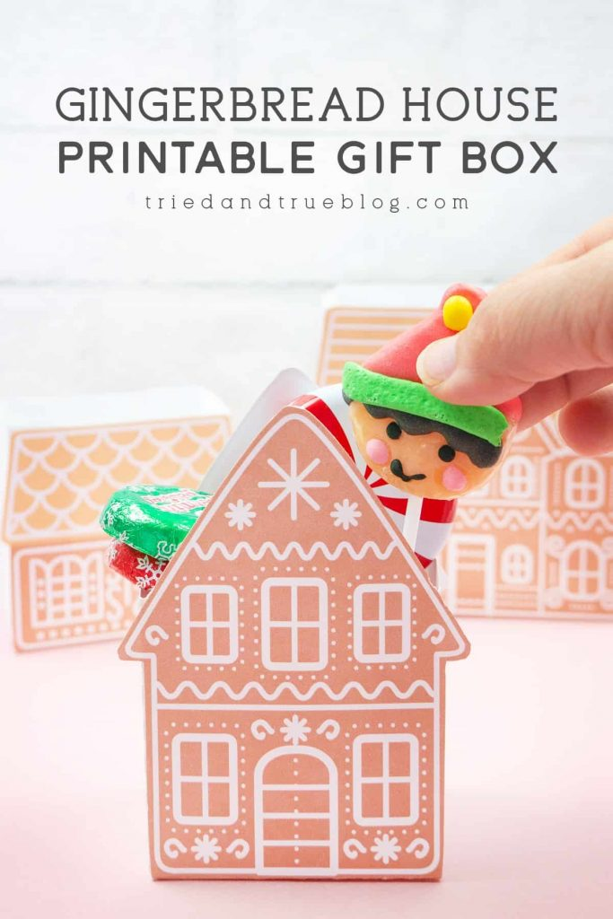 Hand inserting a lollypop into a Gingerbread House Gift Box