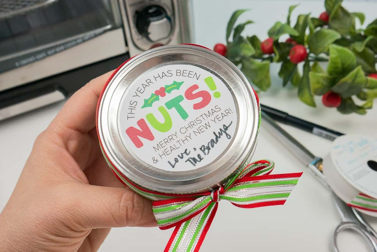 """Hand holding a mason jar with a circular label that says, """"This year has been Nuts! Merry Christmas & Healthy new Year! Love, The Bradys"""""""