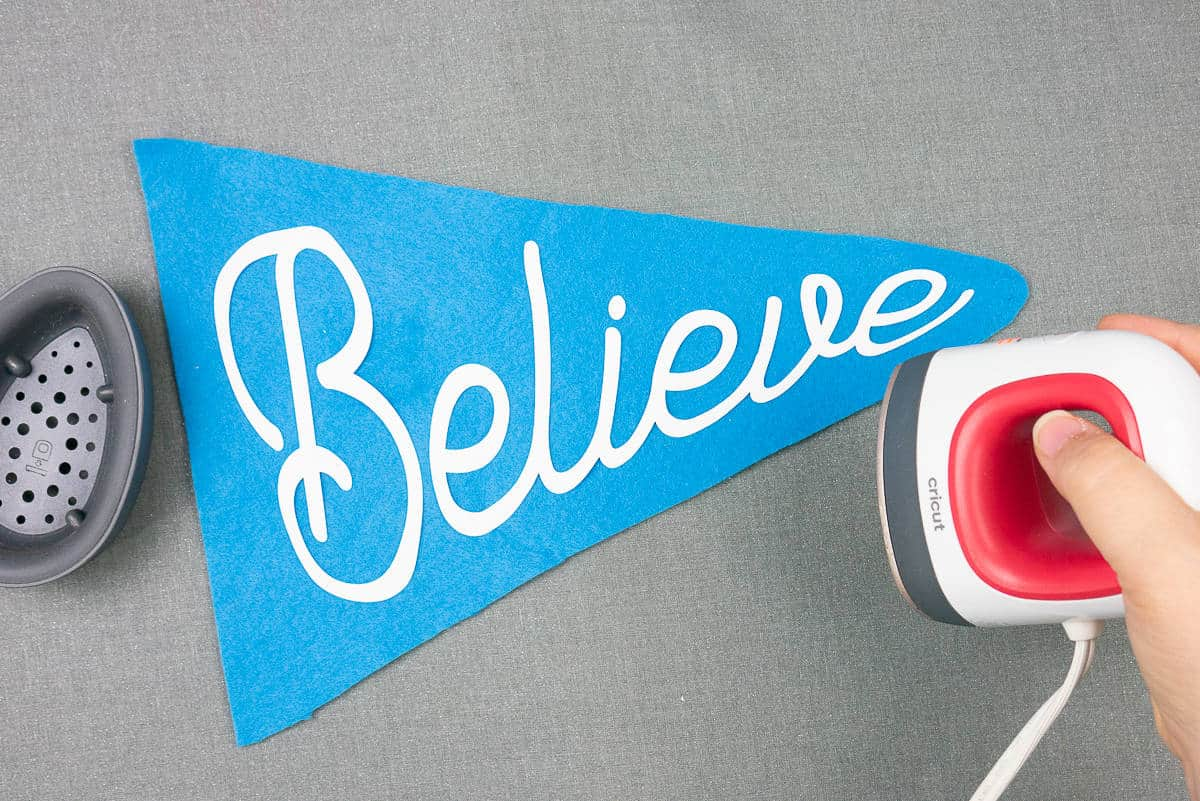 """Hand holding small iron over the a blue flag with """"Believe"""" iron-on."""