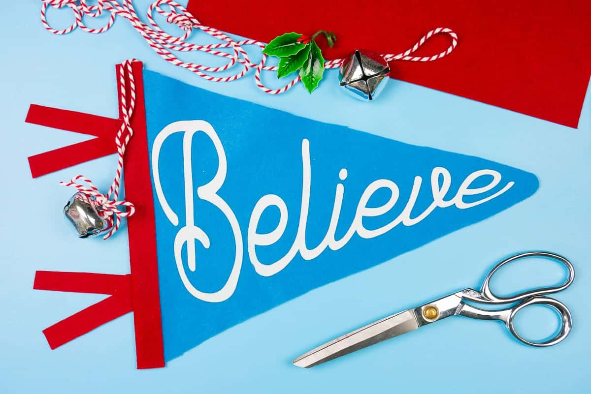 """Blue Christmas Felt Pennant Flag with the word """"Believe"""" in white."""