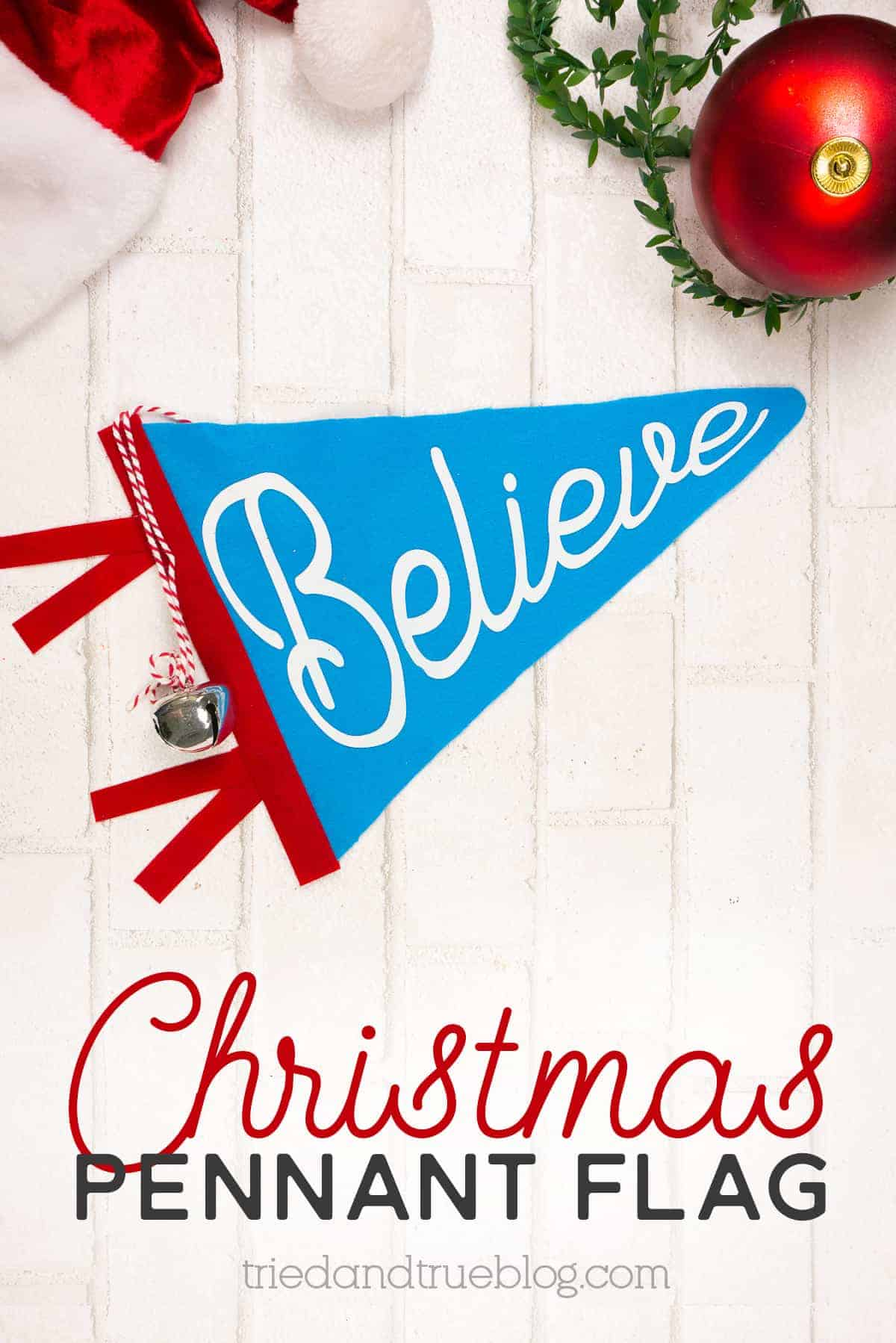Blue Christmas Felt Pennant Flag on a white brick background with various Christmas supplies.