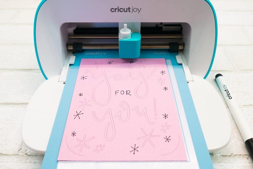 Cricut Joy cutting a pink card.
