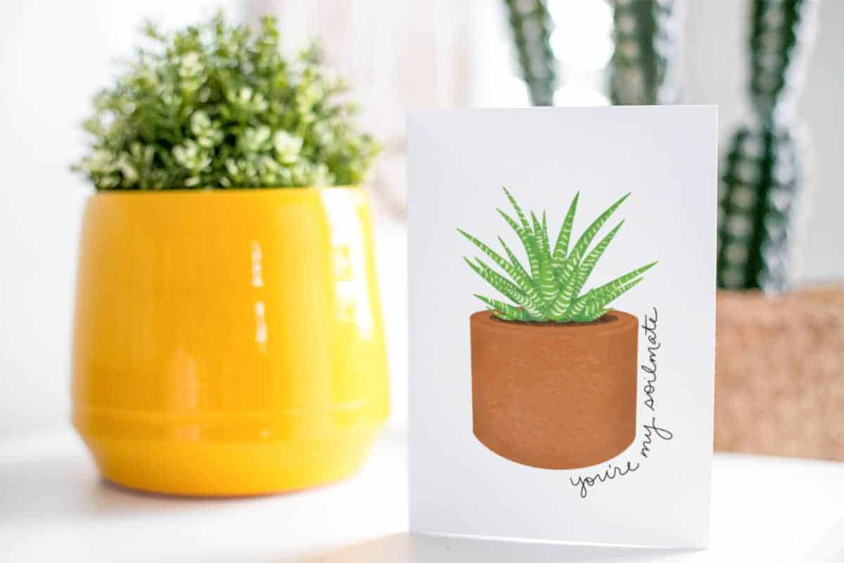 Succulent Valentine's Day Free Printable Card in front of two potted plants.