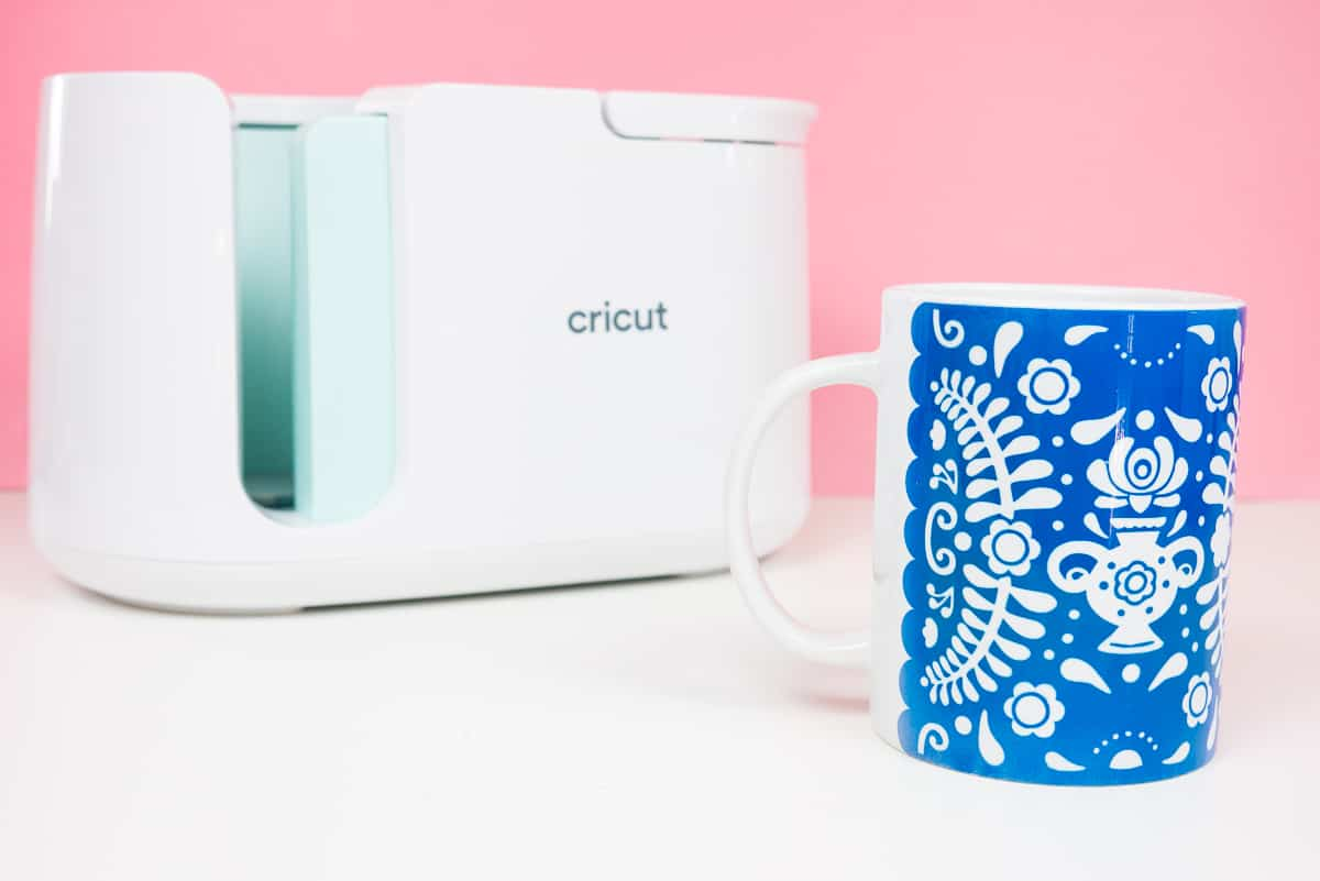 Mug with blue flower pattern in front of Cricut Mug Press on pink background.