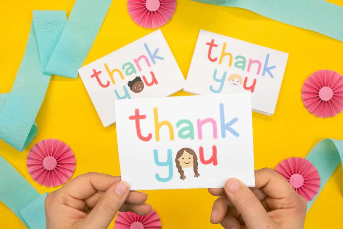 """Hand holding card that says """"thank you"""" with a little kid's face."""