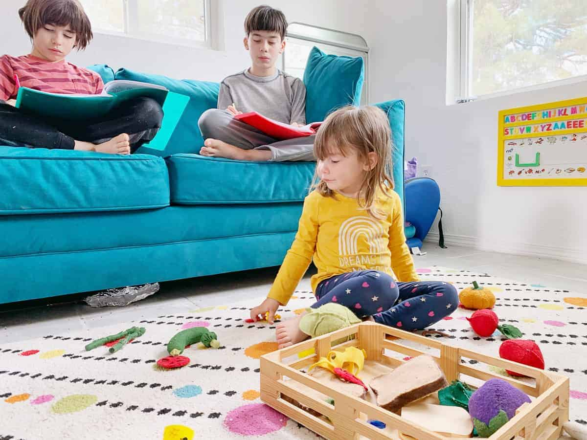 Toddler sitting in front of teal couch with two older boys working on school work.