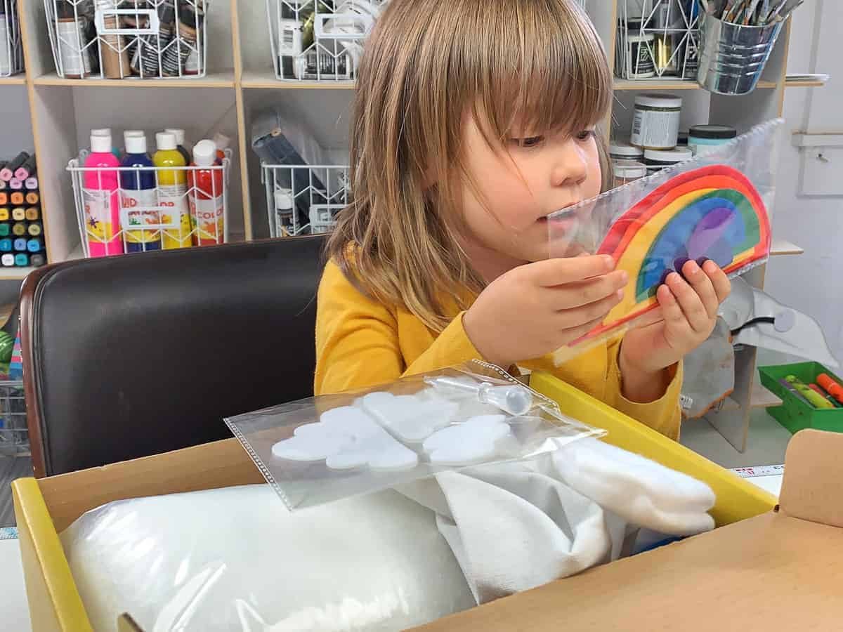 Toddler girl holding felt rainbow stickers from the Koala Crate.