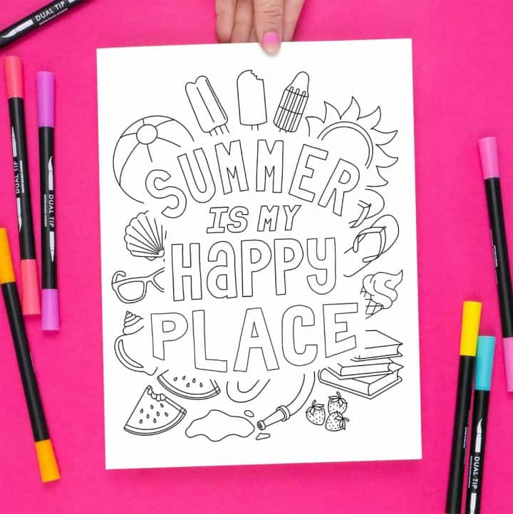 Hand holding the Summer Happy Place Coloring page on a bright pink background, surrounded by markers.