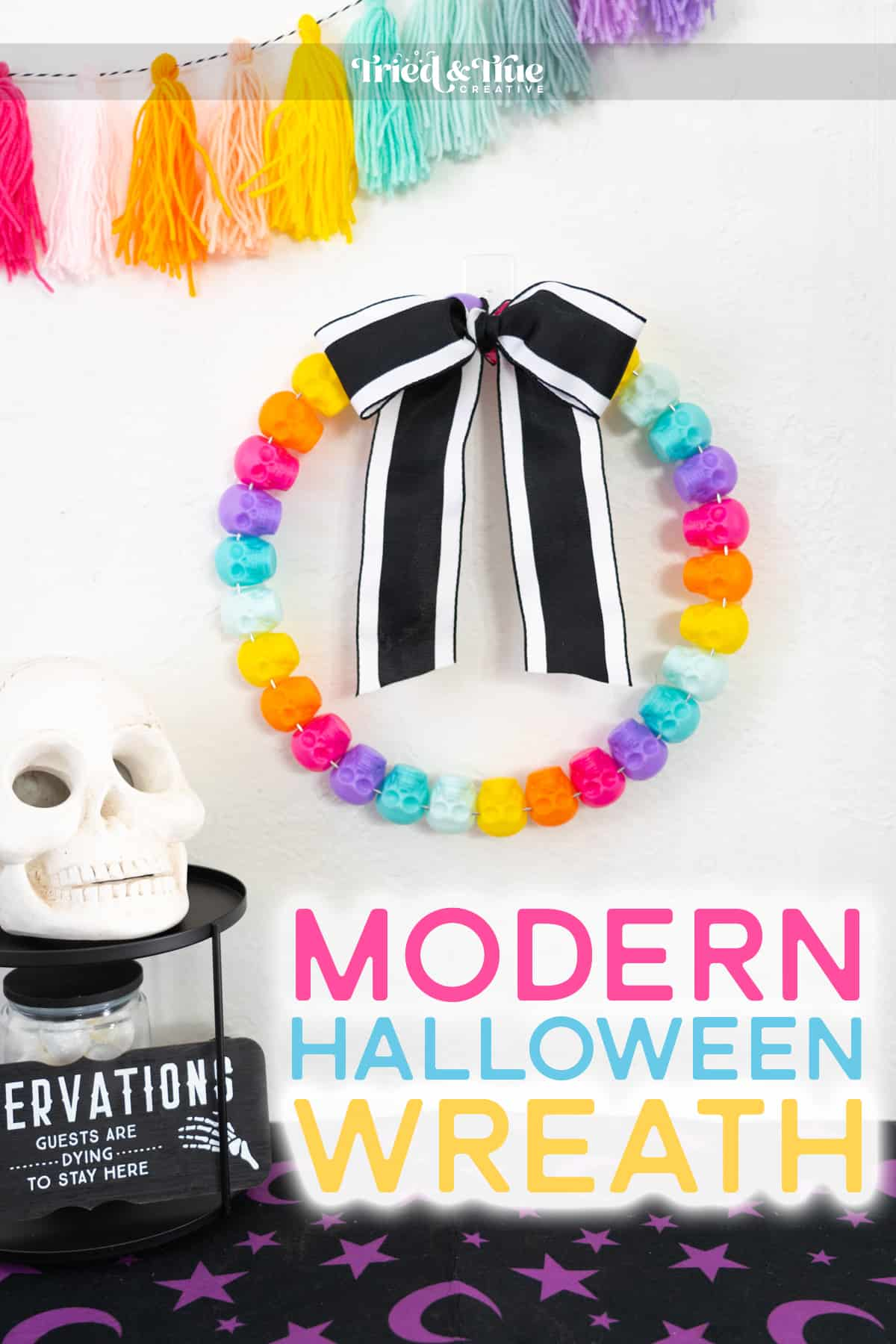 Colorful Halloween Wreath craft made of colorful skulls on a white wall with Halloween decor surrounding it.