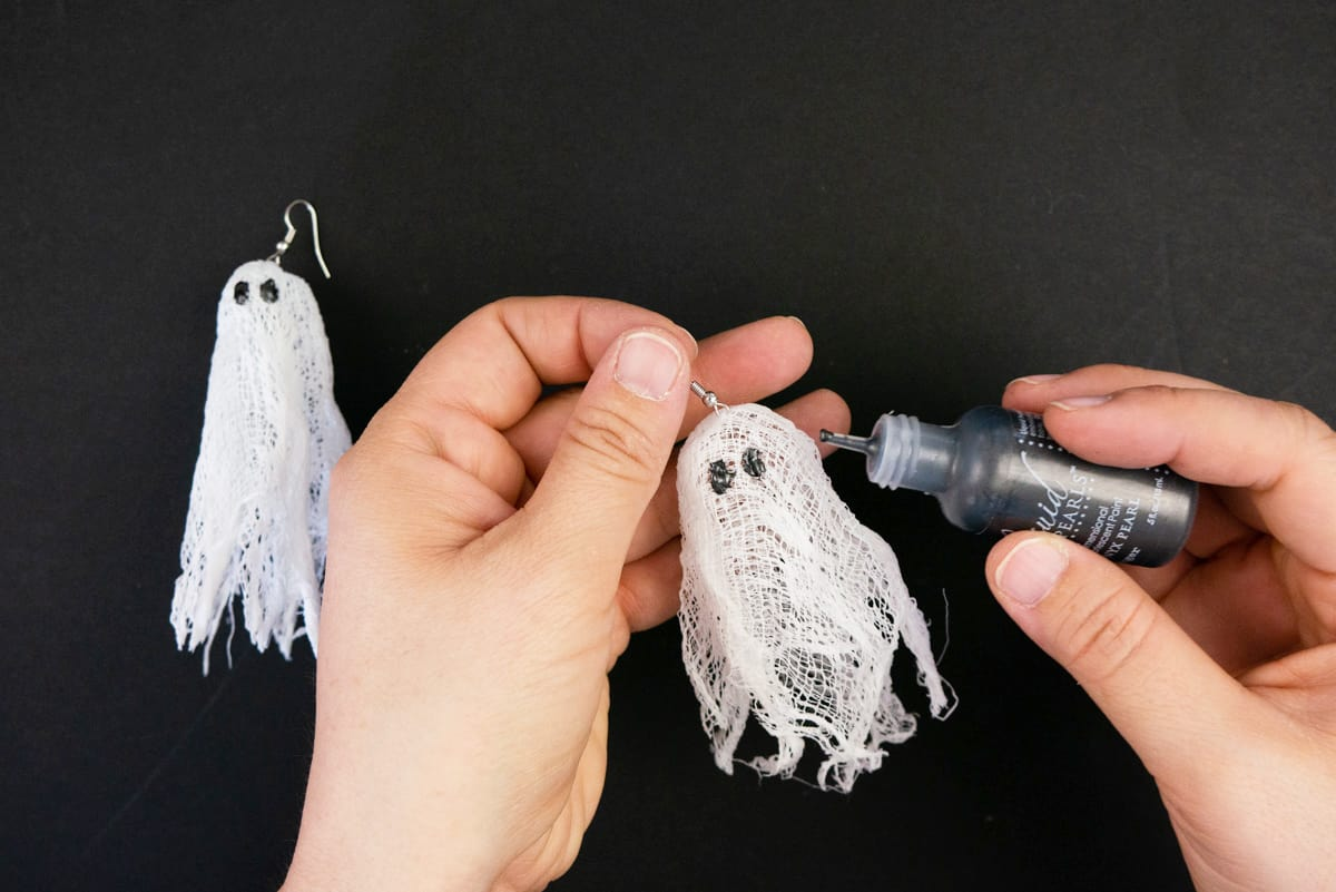 Hands adding black eyes with paint to cheesecloth ghosts.