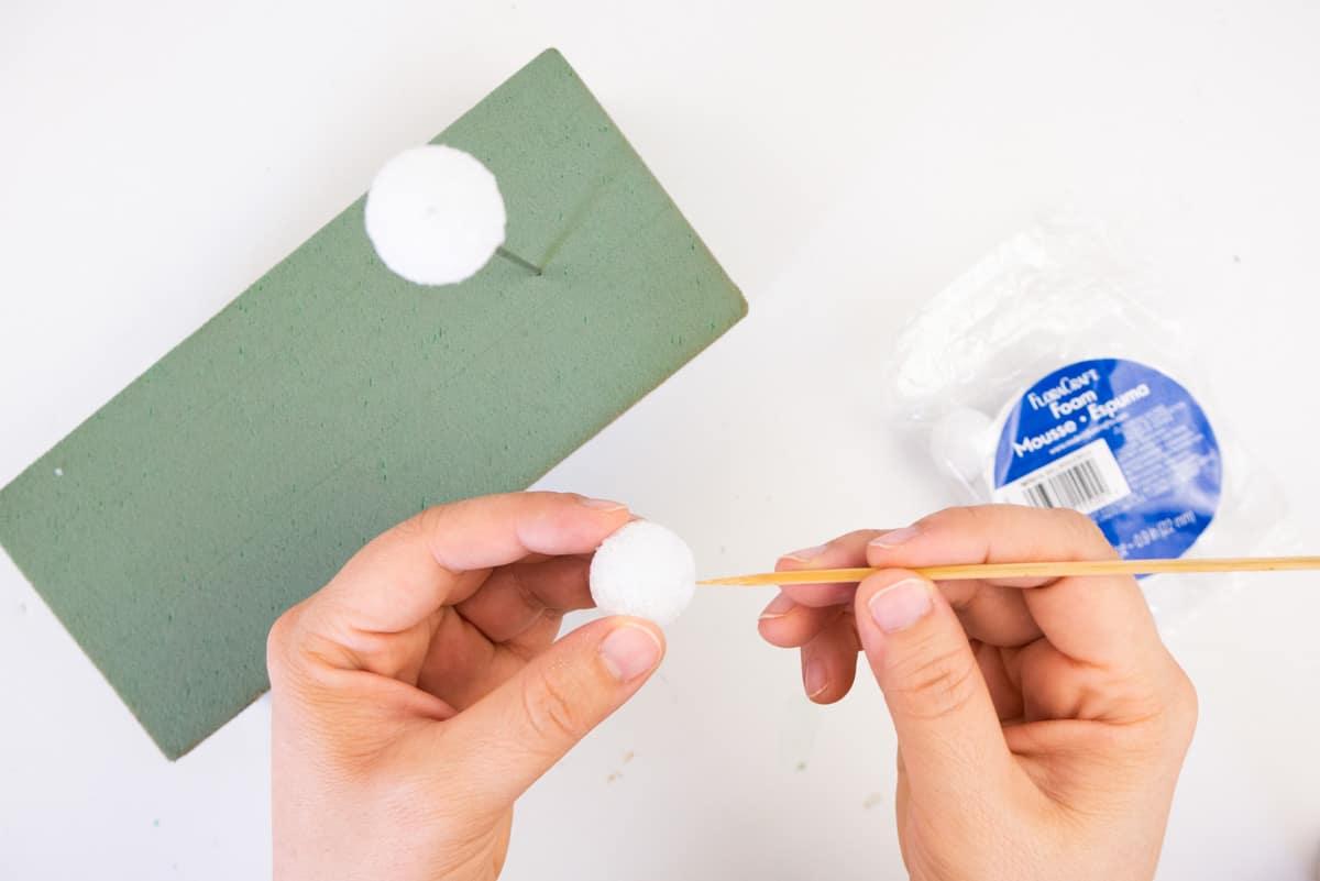 Hand pushing wood skewer into styrofoam ball.