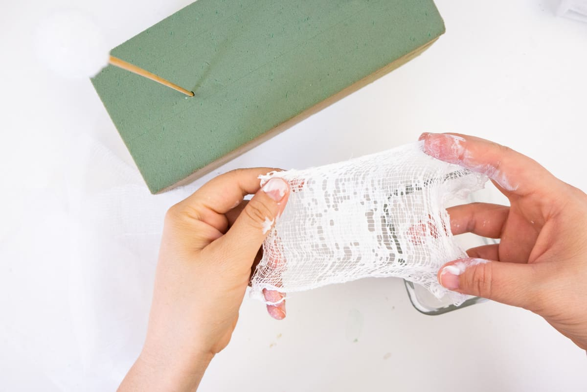 Hands holding cheesecloth with fabric stiffener on it.
