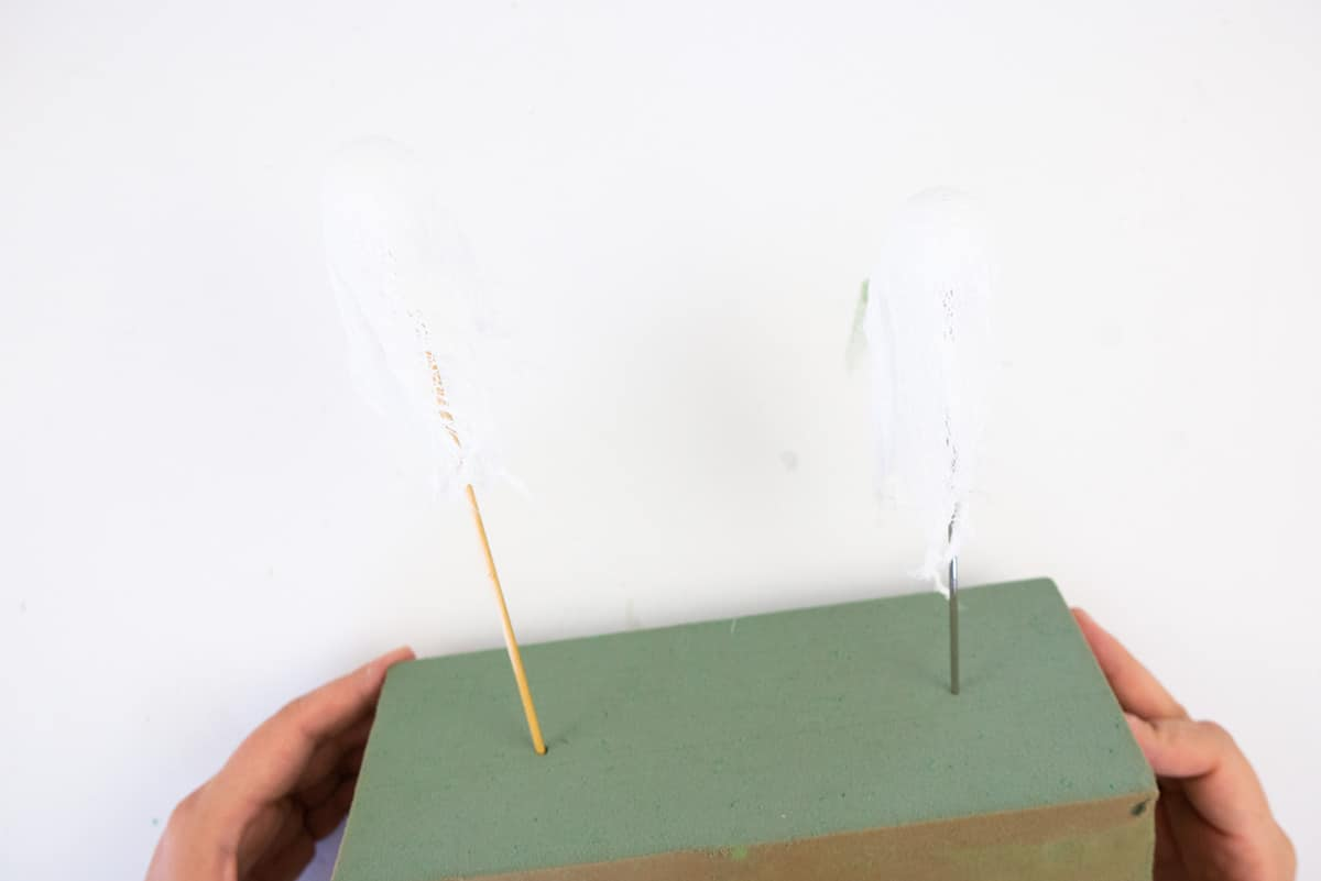 Wood skewers in green foam with small cheesecloth ghosts on it.