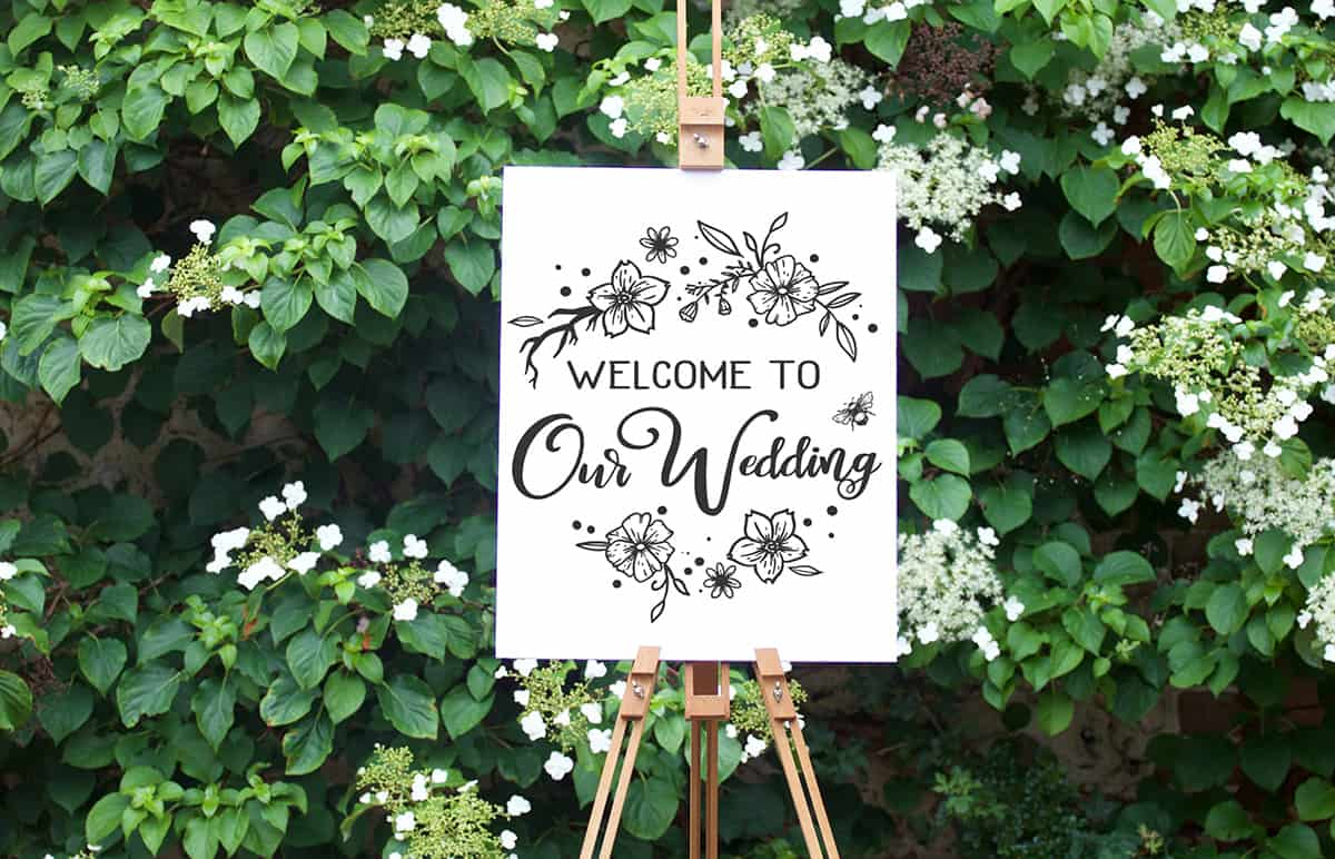 Welcome To Our Wedding free cut file on a white canvas in front of green ivy.